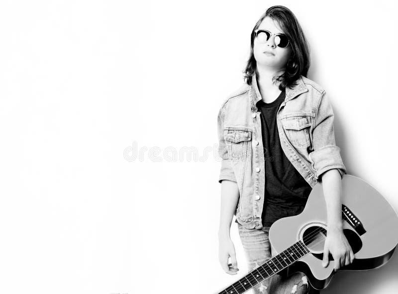 Svartvit stående av den stiliga tonåringen i vit bakgrund som rymmer hans gitarr royaltyfria bilder