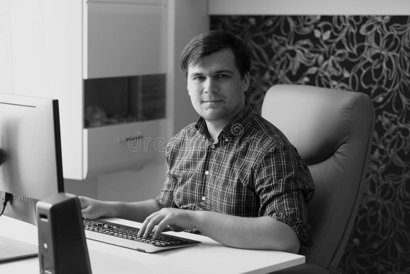 Svartvit stående av den unga mannen som arbetar på hemmastatt kontor för dator arkivfoto