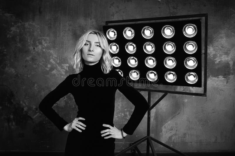 Svartvit stående av den unga stilfulla härliga attraktiva lockiga flickan i svart tröja på etappen arkivfoto