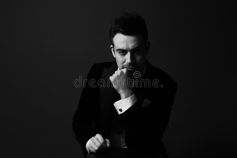 Svartvit stående av en iklädd svart för allvarlig ung stilig man, dramatisk belysning, hand till framsidan royaltyfria bilder