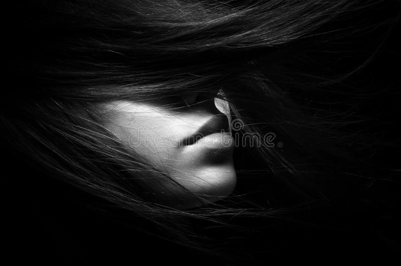 Svartvit stående av flickan på en svart bakgrund arkivfoto