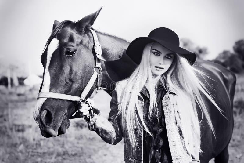 Svartvit stående för tappning av en ung härlig caucasian flicka som rymmer en häst royaltyfri foto