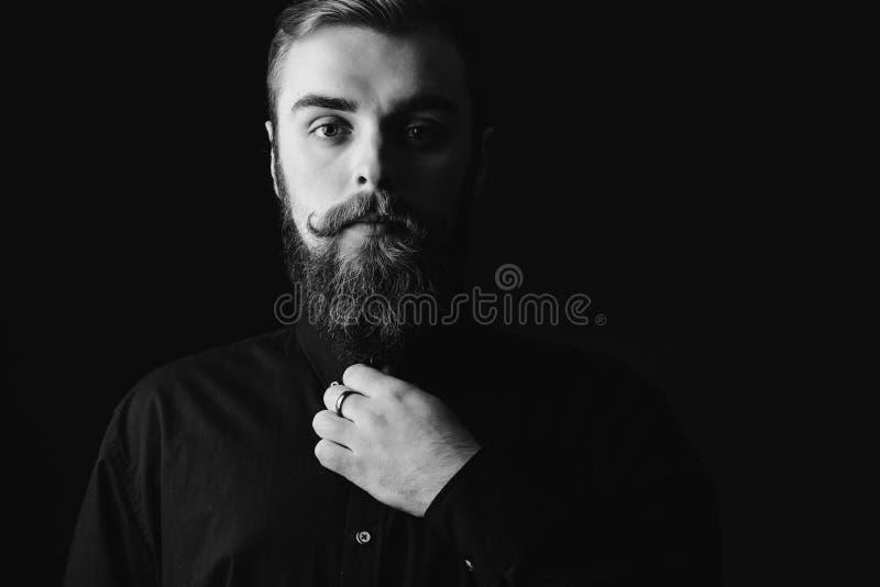 Svartvit st?ende av en stilfull man med ett ikl?dda sk?gg och stilfull frisyr den svarta skjortan p? svarten royaltyfria foton