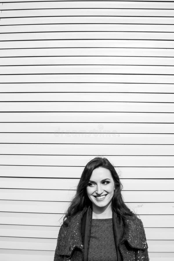Svartvit stads- stående av den fantastiska flickan med sinnliga kanter och yrkesmässig makeup på väggbakgrund arkivfoton