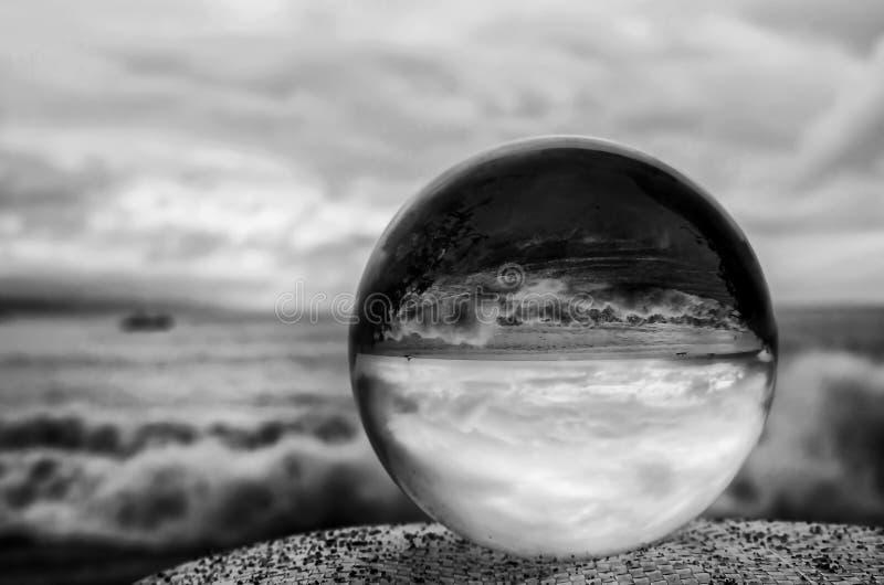 Svartvit stormig bränning och himmel till och med den Glass bollen arkivfoton