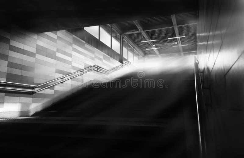 Svartvit tunnelbana uppför trappan med bakgrund för ljusa strålar arkivfoto