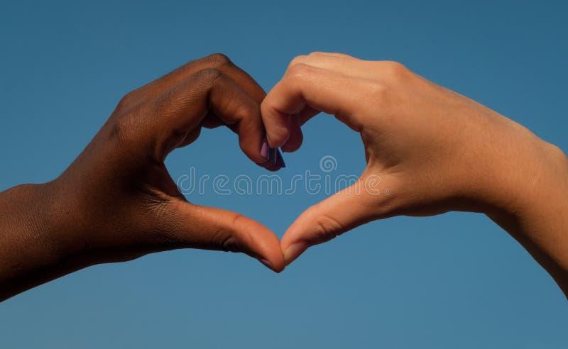 Svartvita händer i hjärta formar, det mellan skilda raser kamratskapbegreppet royaltyfri bild