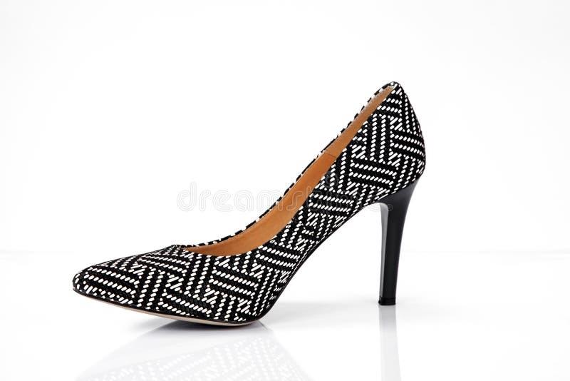 Svartvita skor för kvinnor för hög häl för modell som isoleras på vit bakgrund royaltyfria foton