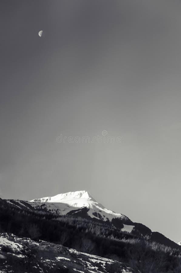 Svartvitt alpint snömaximumberg med månen royaltyfri foto