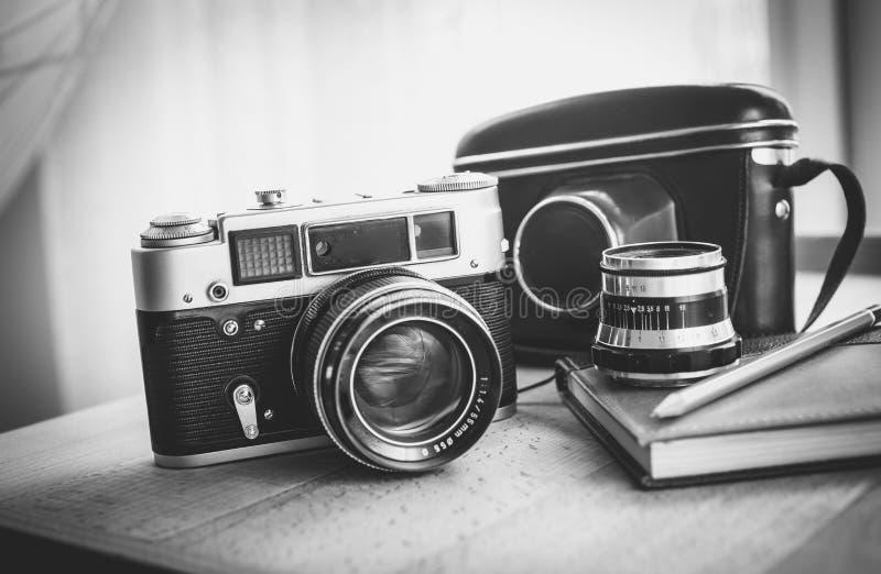 Svartvitt closeupfoto av den gamla kameran och anteckningsbok på skrivbordet royaltyfri fotografi