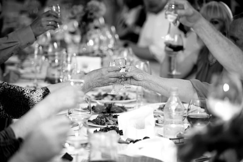 Svartvitt foto av att fira folk som klirrar exponeringsglas arkivbilder