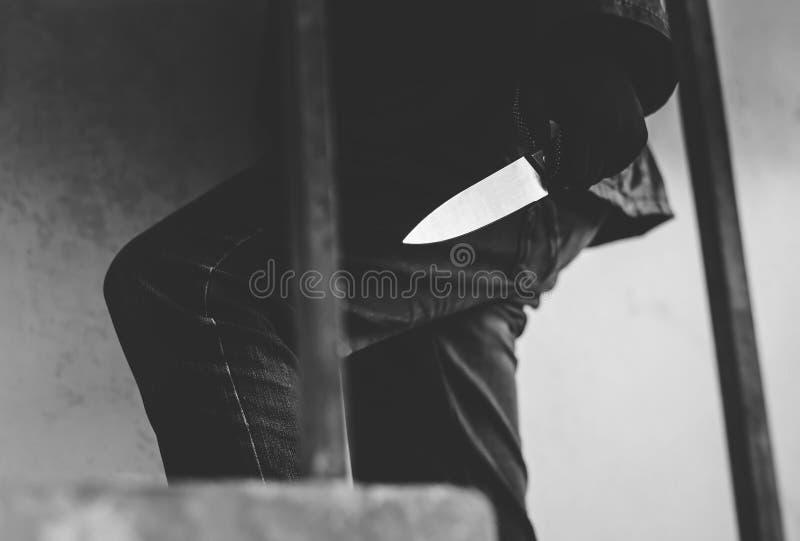 Svartvitt foto av banditen som bär en maskering som går på trappa med en kniv för bytet royaltyfri bild