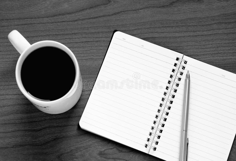 Svartvitt foto av den bästa sikten på den öppnade anteckningsboken, penna och koppen kaffe arkivfoto