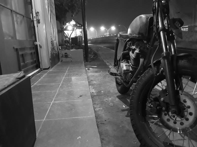 Svartvitt foto av den gamla motorcykeln som framme parkeras av dörren royaltyfri bild