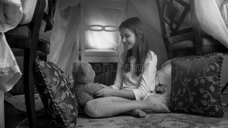 Svartvitt foto av den gulliga flickan som hemma spelar med nallebjörnen i tipitält royaltyfria foton