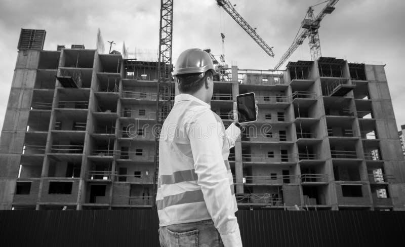Svartvitt foto av den manliga arkitekten med den digitala minnestavlan som arbetar på byggnadsplats arkivfoton