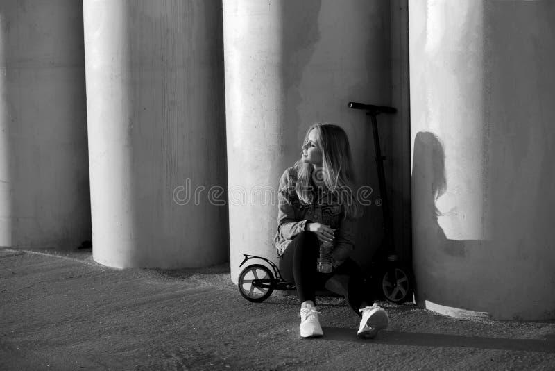 Svartvitt foto av en flicka på en sparkcykel arkivbild