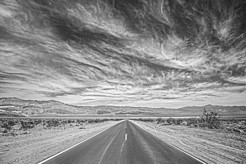 Svartvitt foto av en huvudväg i Death Valley, USA arkivfoto