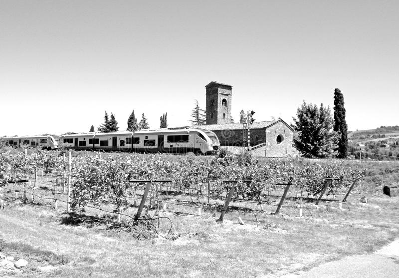 Svartvitt fotografi av ett drev som förbigår en kyrka mellan träd och landet med kiwifältet arkivbild