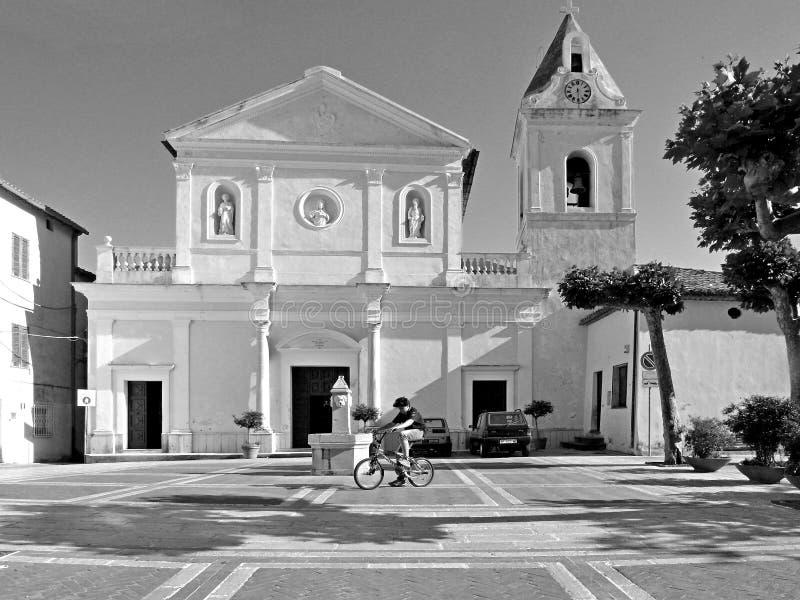 Svartvitt fotografi Tortora: den fyrkantiga kyrkan och behandla som ett barn på cykeln arkivbild