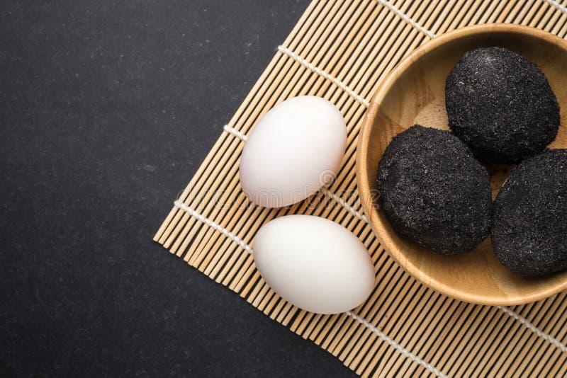 Svartvitt rimmat ägg för thailändsk stil i träbunke på svartst arkivbild