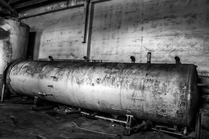 Svartvitt rostat behållaremaskineri i gammal lagerkonservfabrik arkivfoto