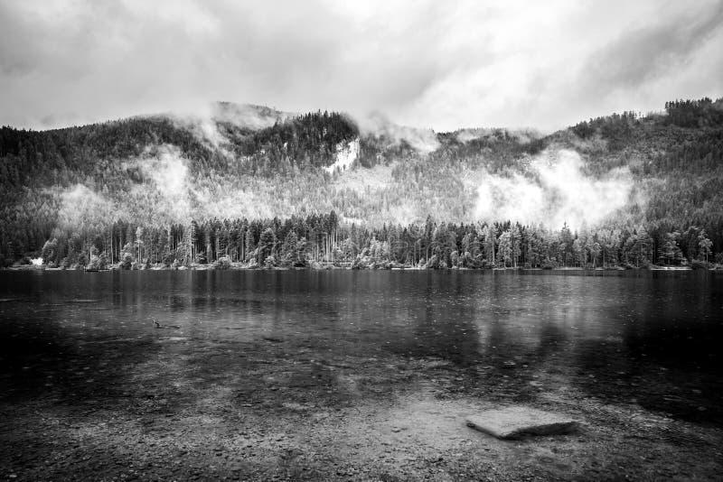 Svartvitt sjölandskap med berg Molnig och dimmig sikt, abstrakt naturpanorama fotografering för bildbyråer