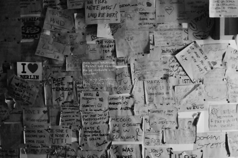 Svartvitt skott av en vägg som täckas fullständigt av klibbiga anmärkningar i italienare fotografering för bildbyråer