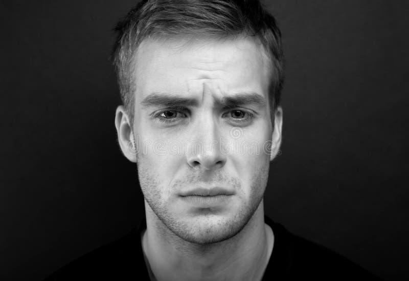 Svartvitt ståendefoto av den unga ledsna mannen royaltyfri foto