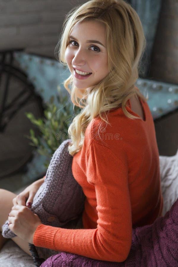 Svegli biondi dimagriscono la donna adatta di affari nel sorridere arancio del maglione C fotografia stock libera da diritti