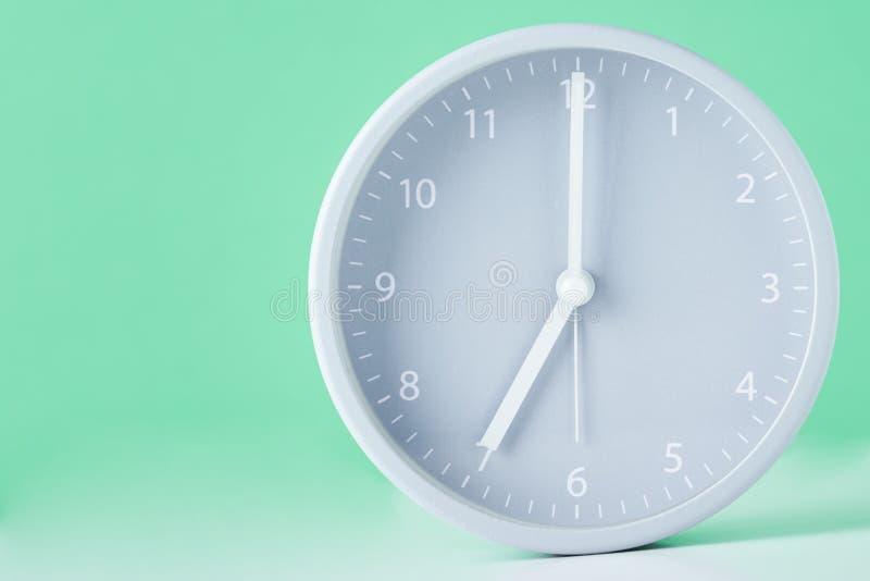 Sveglia classica grigia su un fondo verde pastello con lo spazio della copia fotografie stock libere da diritti