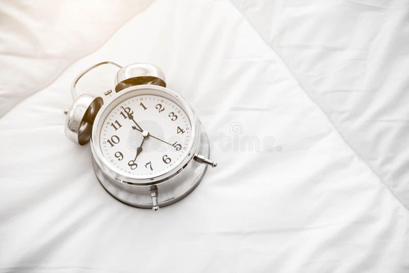 Sveglia di squillo sul lenzuolo bianco Vista superiore di oggetto messa in opera dell'orologio di 8 o fotografia stock libera da diritti
