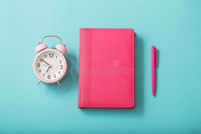 Sveglia e diario su fondo di carta pastello fotografie stock