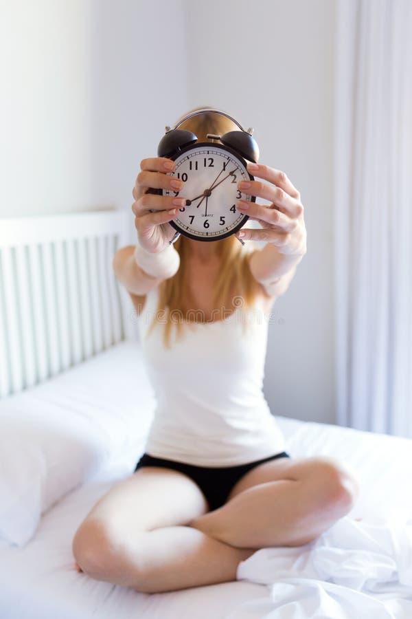Sveglia graziosa e rappresentazione della tenuta della giovane donna alla macchina fotografica nella camera da letto immagini stock libere da diritti