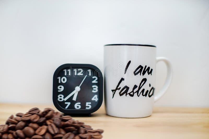 Sveglia nera moderna accanto alla tazza da caffè fotografie stock