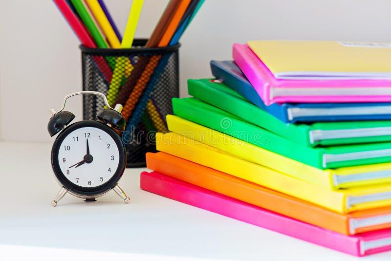 Sveglia nera Multi libri colorati in pila fotografie stock libere da diritti