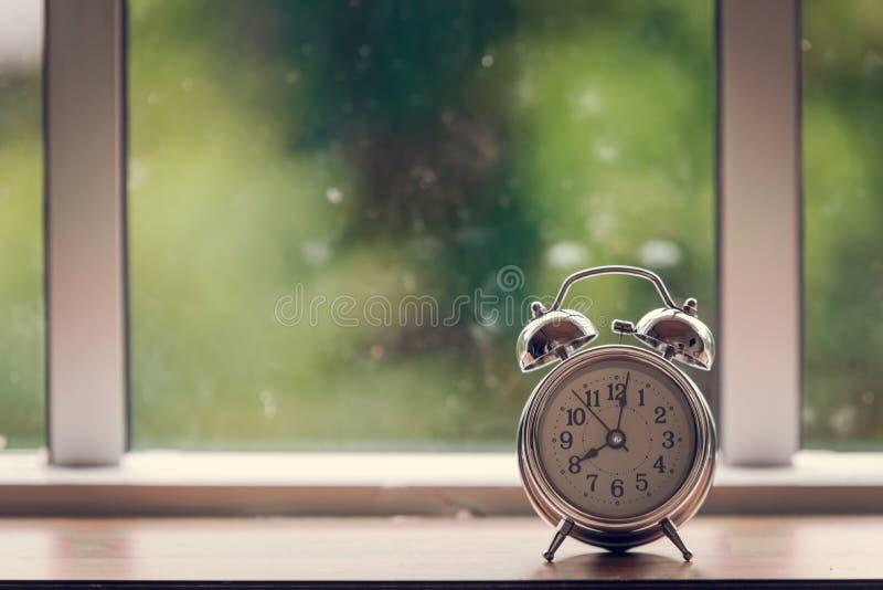 Sveglia sulla tavola di legno e sulla finestra di vetro immagine stock libera da diritti