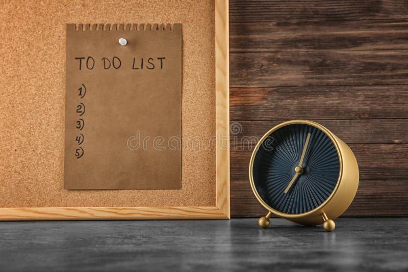Sveglia sulla tavola e sul foglio di carta con la lista di da fare a bordo Concetto della gestione di tempo fotografia stock