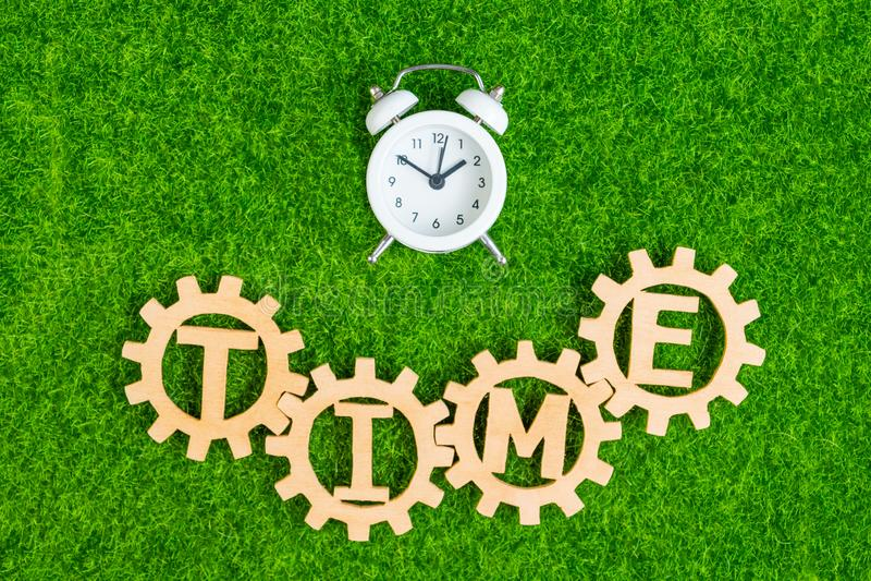 Sveglia, tempo, ingranaggi di legno sui precedenti di erba verde artificiale fotografia stock libera da diritti