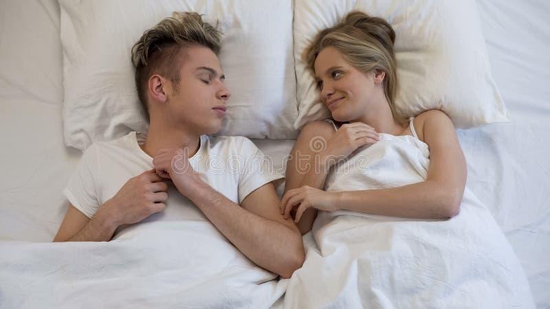 Svegliare femminile adolescente e tenero esaminare il suo ragazzo addormentato, amore immagine stock