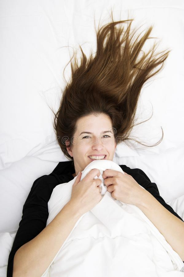 Svegliarsi divertente La giovane donna sta trovandosi nel suo letto, nel sorridere e nello scherzare immagine stock
