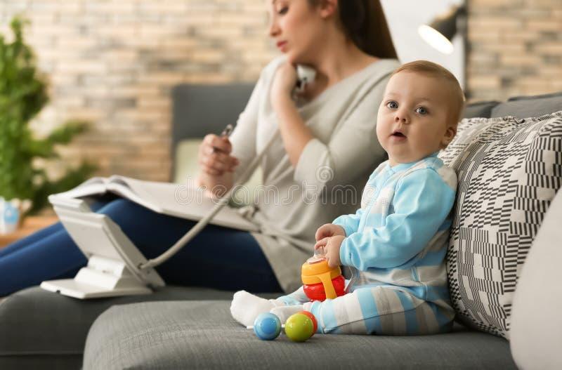 Sveglio poco fare da baby-sitter sul sofà mentre madre che lavora a casa fotografia stock libera da diritti