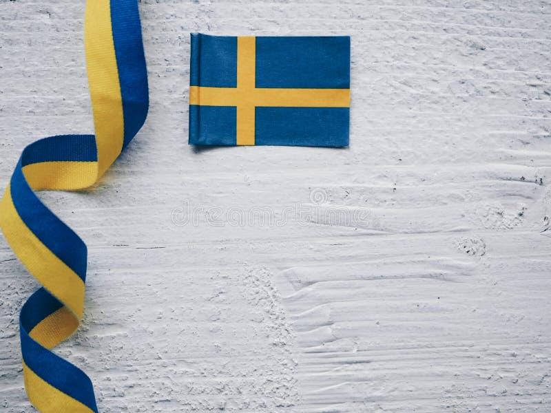 Svensk flagga och band p? vit tr?bakgrund arkivbild