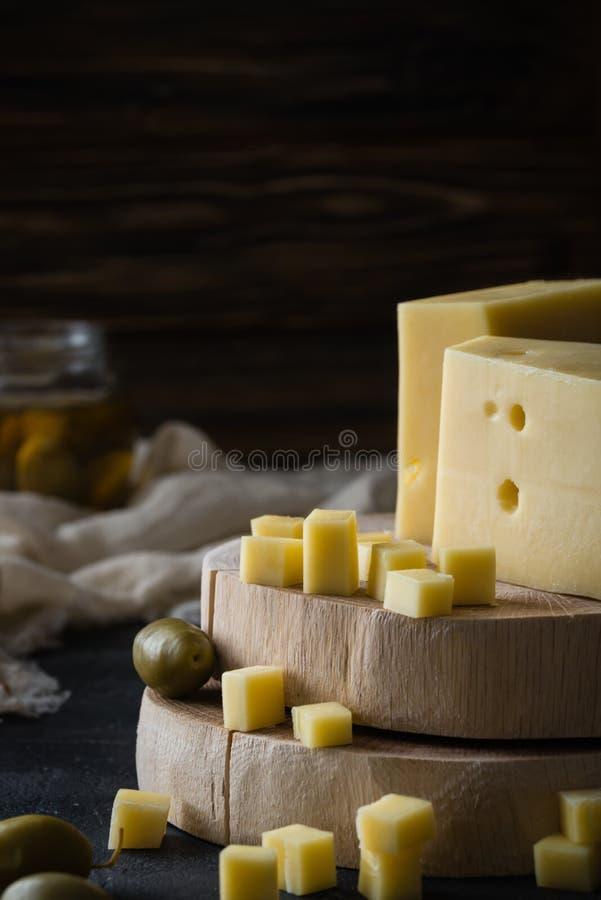 Svensk hård gul ost med hål högg av på träskivor med gröna oliv arkivfoton