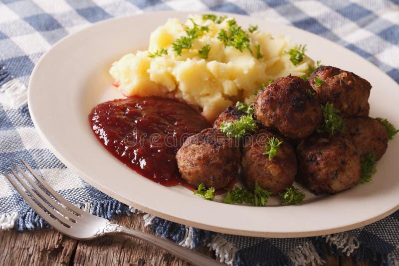 Svensk mat: köttbullar lingonsås med potatisgarnering royaltyfri fotografi