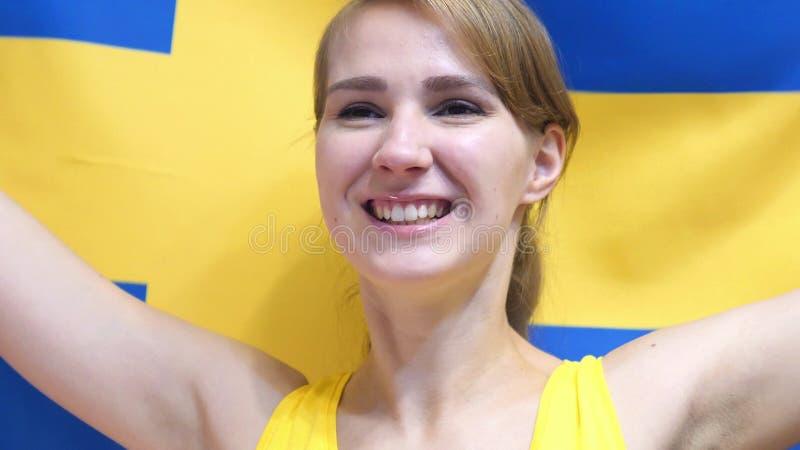 Svensk ung kvinna som firar, medan rymma flaggan av Sverige i ultrarapid fotografering för bildbyråer
