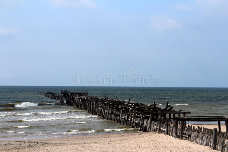 Sventoji Beach Pier Ruin Small Waves Blue Sky. Empty idyllic Lithuanian beach of Sventoji showing one larger of the two pier ruins along the rolling golden sands royalty free stock image