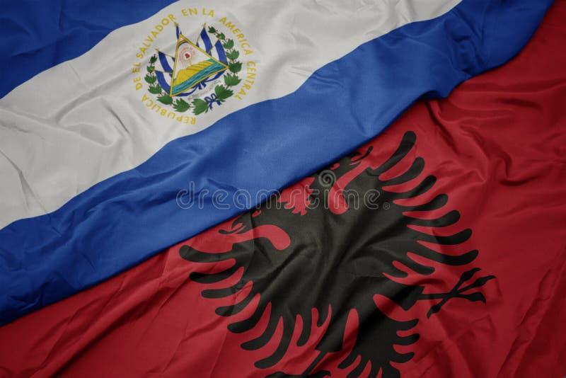 sventolando bandiera albanese colorata e bandiera nazionale di el salvador fotografia stock libera da diritti