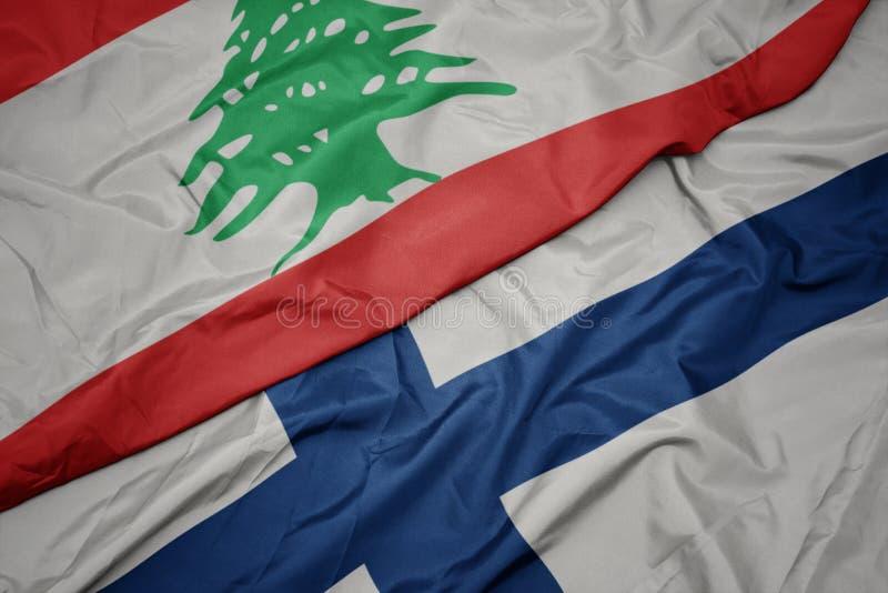 sventolando bandiera finlandese colorata e bandiera nazionale libanese immagine stock libera da diritti