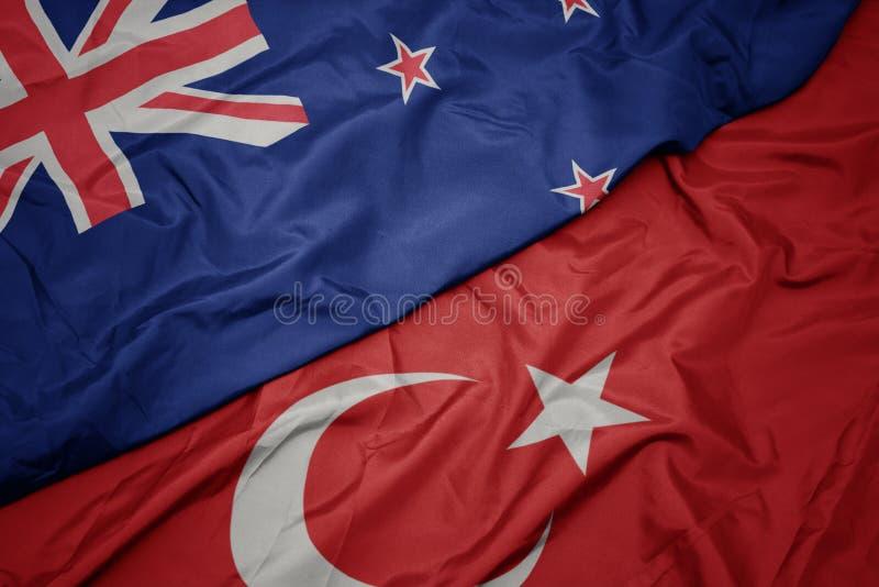 sventolando la bandiera colorata del tacchino e la bandiera nazionale del nuovo zealand immagini stock